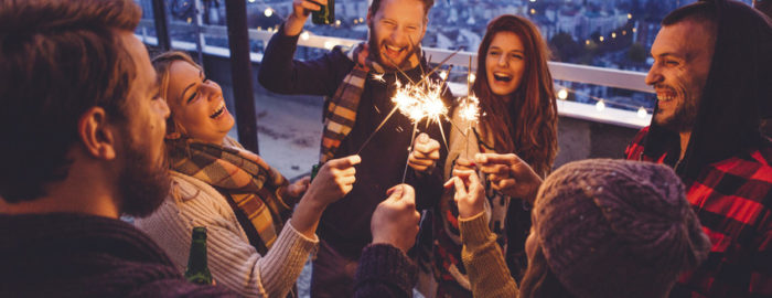 group of friends with sparkles on roof top celebrating new years eve.