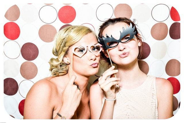 two women hold up masks to their face against a photo booth background.
